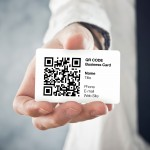 Businessman holding QR code business card with personal data. Modern technology concept.